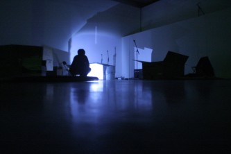 A shadow crouches on the floor amongst mic stands and boxes, one light source