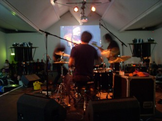 Three blurry dark band members play in front of a projection