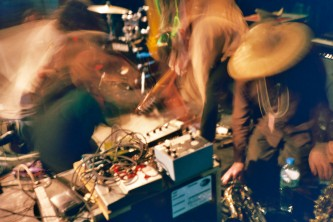 Three blurry musicians bend over their instruments on a stage full of equipment