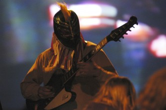 Sunburned hand of the man guitarist in a mask playing a guitar