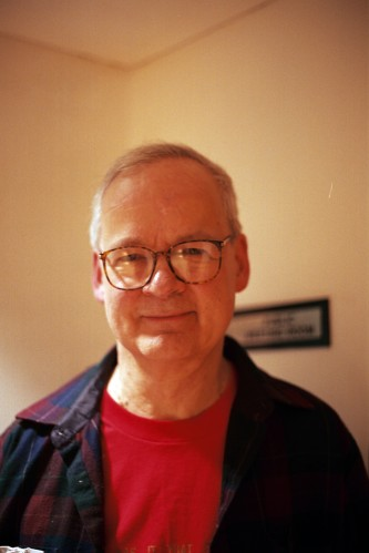 Tony Conrad portrait, backstage wearing glasses and a purple shirt