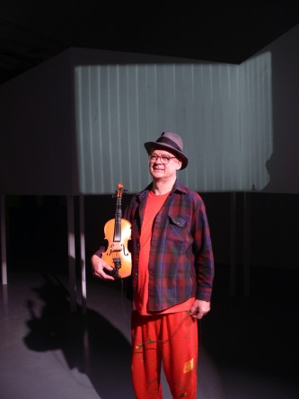 Tony Conrad standing with a violin in hand against a screen, in orange clothes
