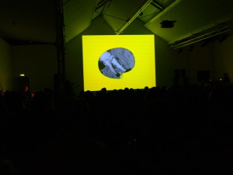 A person's legs framed in lemon yellow on a screen before an audience