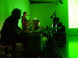 Musicians in green light; drummer, saxophonist, someone in the distance