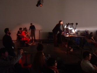 musicians positioned behind projectors in an auditorium, audience in foreground