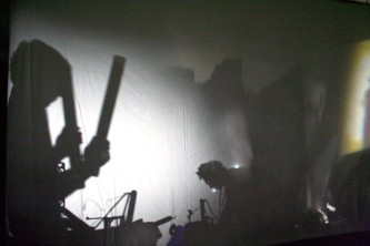silhouettes of musicians behind a screen