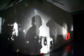 The corner of a large cube of fabric with light casting shadows from within