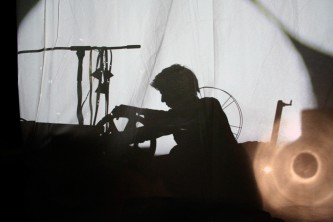 A silhouette of a man against a sheet lit from behind