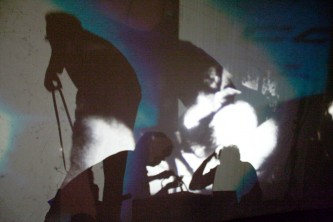 Figures moving around behind a screen lit from within by projectors