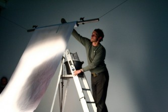 A man up a ladder holds a long sheet of paper in the air