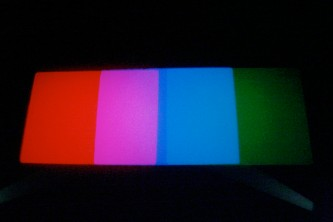 Bands of red pink blue and green light on a screen