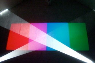 Bands of red pink blue and green light on a screen with beams of white in front