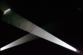 Beams of white light crossing in front of a dark screen