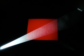 A red rectangle a beam of white light in front