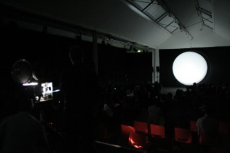 A white balloon lit by a projector some orange chairs in the foreground