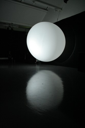 A large white balloon and its reflection in a shiny floor