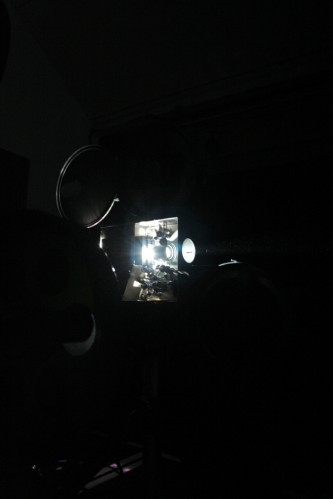 A projector seen from the side, its mechanism glowing