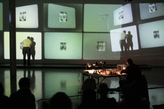 Malcolm Le Grice over by the projection screen, a feedback loop of images