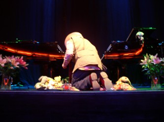 Charlemagne Palestine kneeling among soft toys between 2 pianos