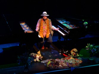 Charlemagne Palestine playing two pianos surrounded by soft toys