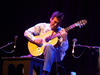 Kazuo Imai playing an acoustic guitar with a chain in his mouth
