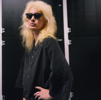 A man with sunglasses and long blond hair poses in front of black cupboards