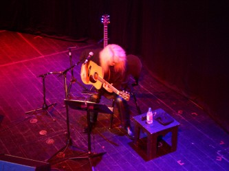 Shuji Inaba on stage at MLFC 07 playing acoustic guitar