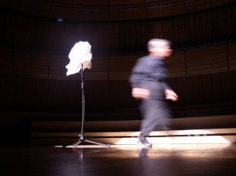 Takehisa Kosugo walking away from a microphone wrapped in paper
