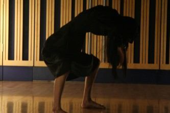 A woman bent over with low centre of gravity during a dance performance