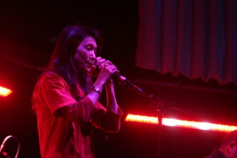Junko singing into a microphone in a t shirt on stage at MLFC 07
