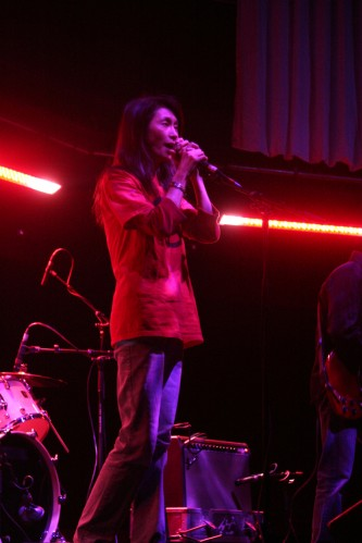 Junko singing into a microphone on stage at MLFC 07