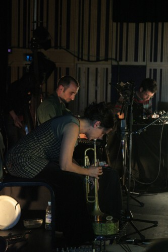 Ruth Barberan playing a trumpet downwards next to Alfreo and Ferran