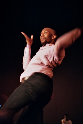 A man in pink jumper with his hands out mid pose on a runway