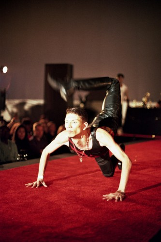 A thin man kneeling on a red carpet leg raised facing forwards intently