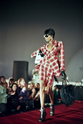 A very well dressed woman walking down a catwalk holding a bag