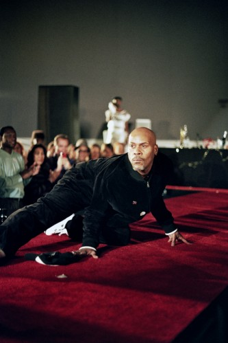 a man looking intently down the length of a red carpet, hands on the ground