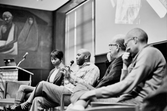 A panel of four folks sit as one with a beard speaks