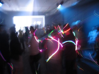 Lights whirl around shadowy figures in a basement party