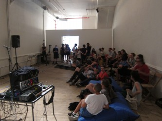 A shot of an audience sat in chairs and on the floor in a gallery