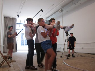 A group of people carry another person as a film crew film them