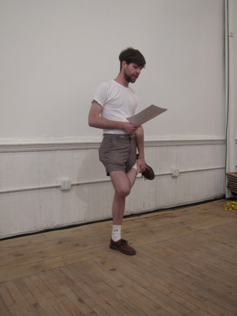 A person stands on one foot as they hold a paper and read