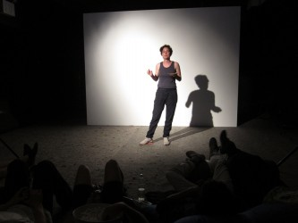 A person stands in a spotlight and talks to an audience