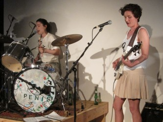 """A drummer plays a set that says """"Penis"""" and a guitarist plays beside her"""