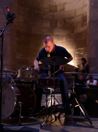 Chris Corsano playing drums and blowing a tube inside Hamilton Mausoleum