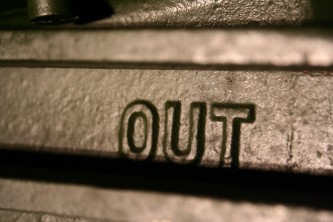 Close up of a metallic form with the word 'OUT' in relief