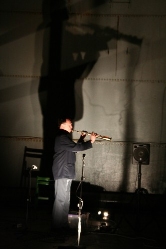 John Butcher and silhouette playing saxophone in an oil tank