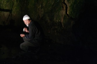 Akio Suzuki tapping stones together in the entrance to a cave
