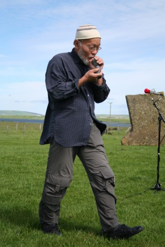 Akio Suzuki blowing into a small object outside on some grass