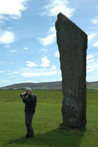 Akio Suzuki blowing into a metal can next to a large standing stone