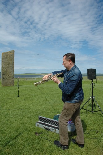 John Butcher holding a soprano sax at an odd angle by standing stones & speakers